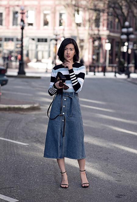 Модель в джинсовой юбке миди, кофточка в горизонтальную полоску, черные босоножки