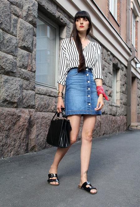 Модель в джинсовой юбке на пуговицах, белая блузка в черную вертикальную полоску, шлепки и черная сумка