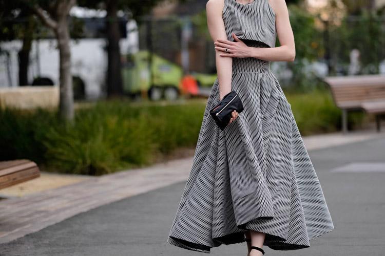 Модель в платье с юбкой клеш без рукавов