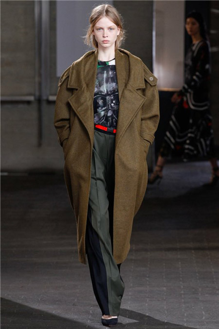 Модель в серых брюках и пальто цвета хаки
