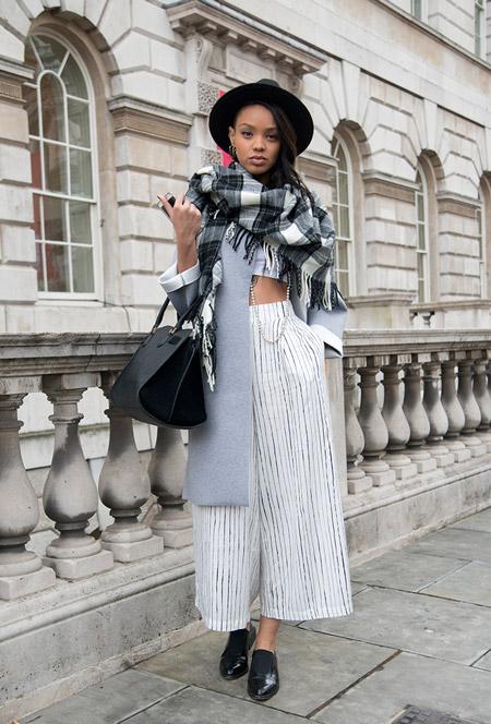Модель в широких брюках, кроп топ, серое пальто, шляпа и шарф в клетку