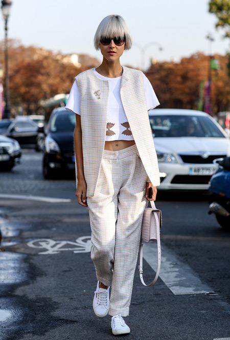 Модель в светлом костюме с брюками и жакетом без рукавов, белый кроп топ
