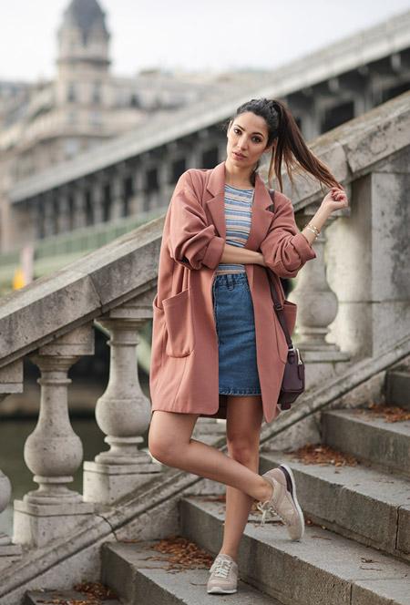 Модель в светлой джинсовой юбке, полосатая футболка, розовое пальто и кроссовки