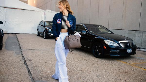 Модель в светлых брюках, полосатый кроп топ и синяя олимпийка