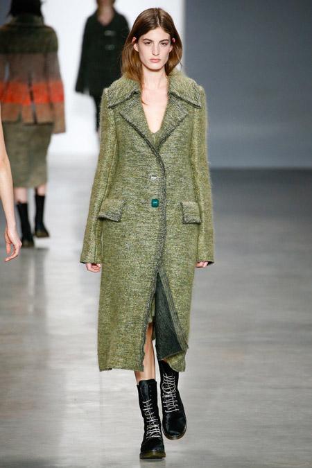 Модель в зеленом пальто и ботинках