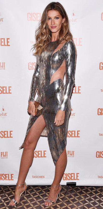 Жизель Бюндхен в блестящем платье в вырезами и серебристых босоножках