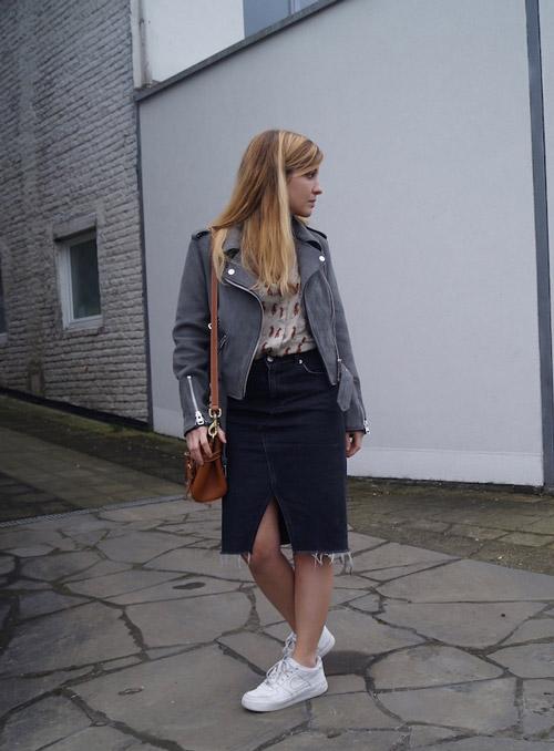 Девушка в белых кроссовках, темной джинсовой юбке и косухе