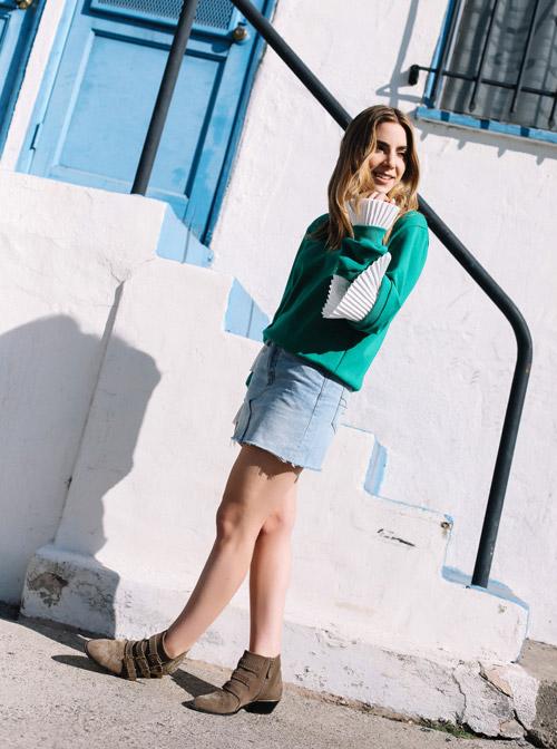 Девушка в голубой мини юбке, ботильонах и зеленом свитере