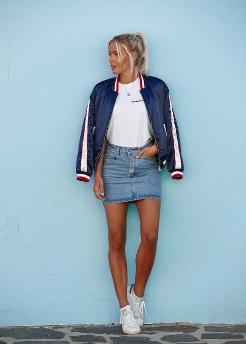 Девушка в джинсовой мини-юбке, белых кроссовках и бомбере