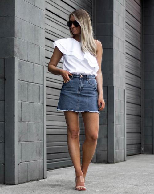 Девушка в белом асимметричном топе, джинсовой юбке и шлепанцах