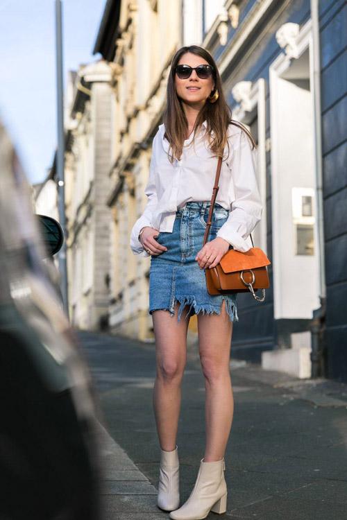 Девушка в джинсовой мини юбке, белой блузе и ботильонах
