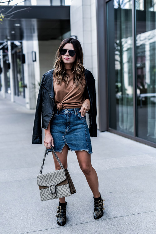 Девушка в черной косухе, джинсовой юбке и ботильонах
