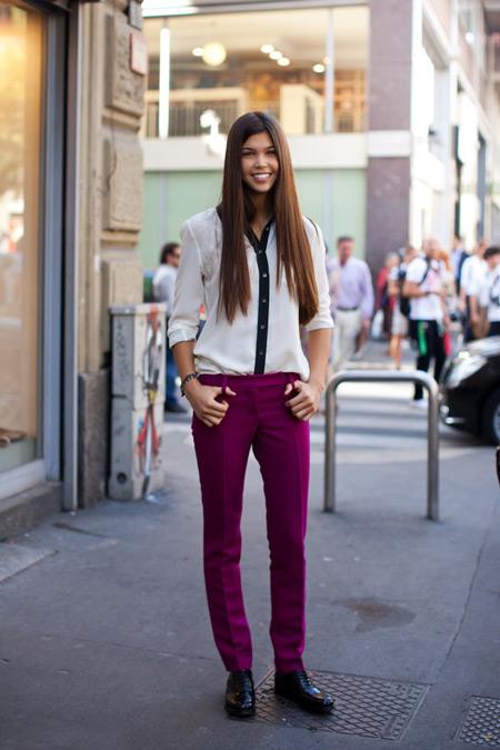 Девушка в бело-черной блузке и бордовых джинсах