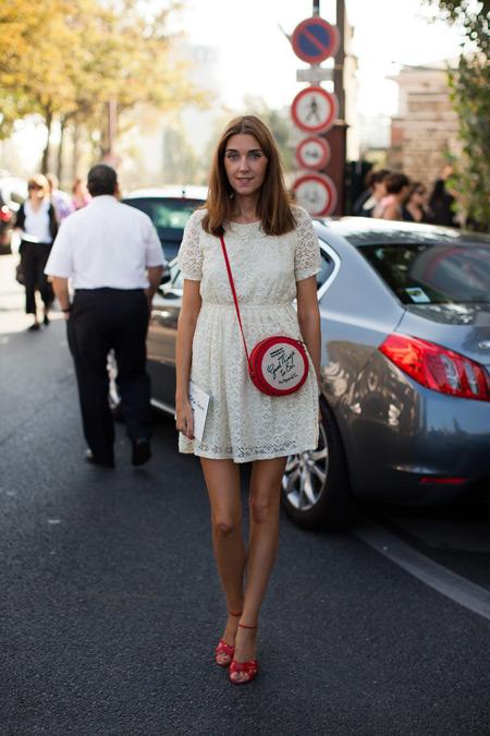 Девушка в белом платье и с красной сумкой