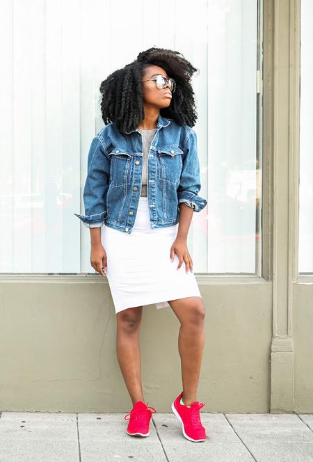 Девушка в белой юбке, серая футболка, джинсовка, розовые кроссовки