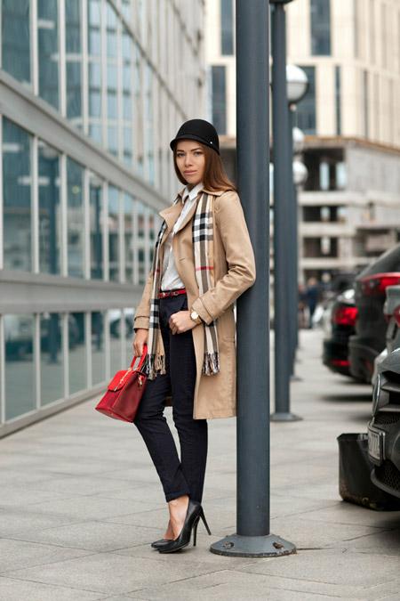 Девушка в бежевом пальто и черных туфлях на каблуке