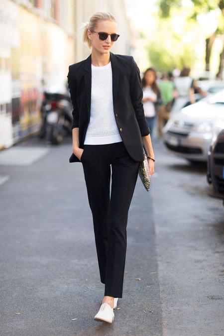 Девушка в черном костюме и белых брогах