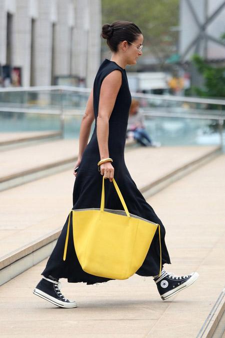 Девушка в черном макси платье, кеды и желтая большая сумка