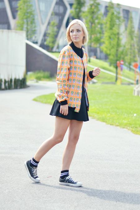 Девушка в черной юбке, оранжевый жакет и кеды