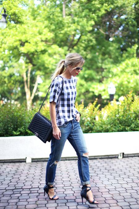 Девушка в джинсах бойфрендах, серая клетчатая футболка и черные босоножки