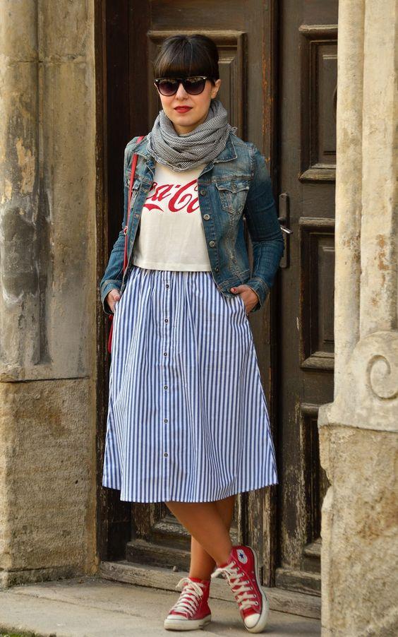 Девушка в голубой юбке миди, белый топ, джинсовка и красные кеды