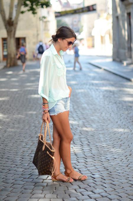Девушка в голубых шортах, белая рубашка, бежевые сандалии и коричневая сумка