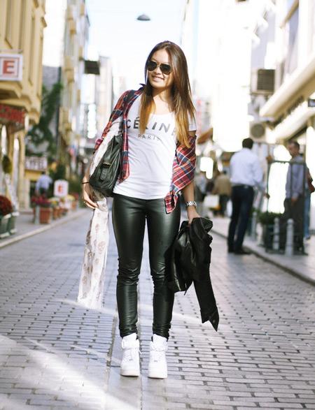 Девушка в кожаных леггинсах и белых сникерсах