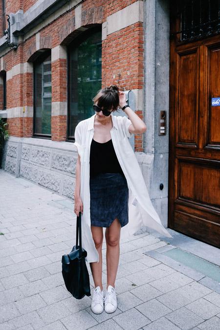 Девушка в прямой юбке, черный топ и легкая белая накидка