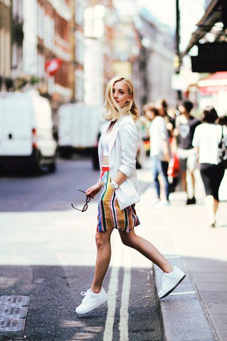 Девушка в разноцветной полосатой юбке, белый топ, пиджак и белые кеды