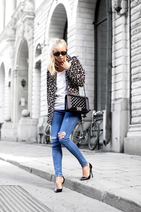 Девушка в рваных джинсах и черных лакированных туфлях
