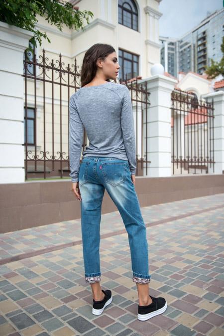 Девушка в сером джемпере и укороченных джинсах