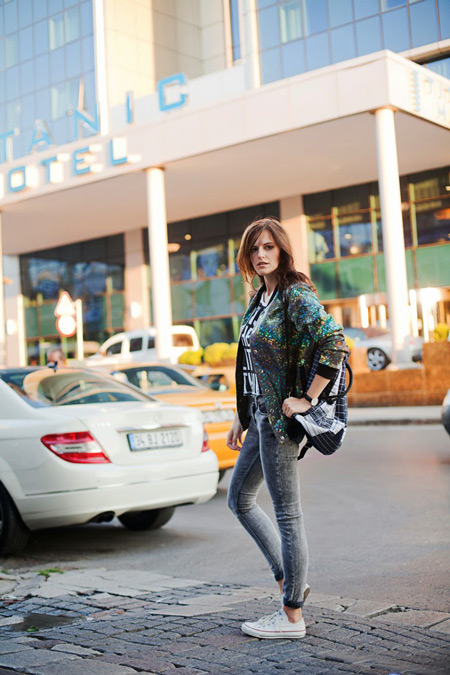 Девушка в серых джинсах, разноцветный бомбер и светлые кеды