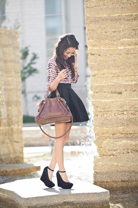 Девушка в юбке и черных туфлях на танкетке