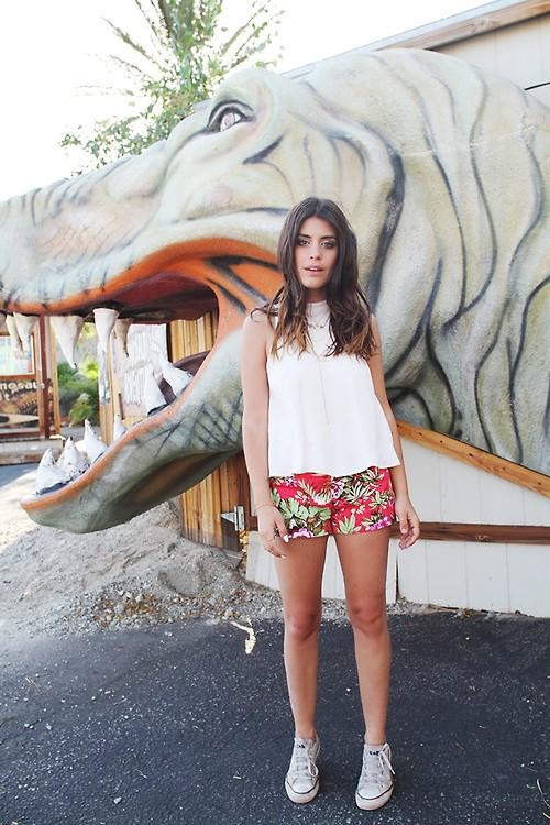 Девушкав красных мини шортах и белом топе, светлые кеды