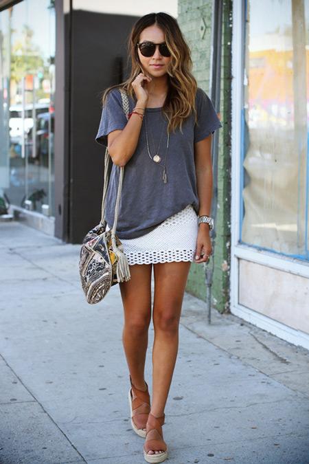 Модель в белой мини юбке, серой футболке и босоножки на платформе
