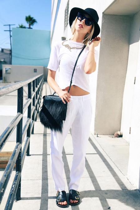 Модель в белых штанах, футболка, черная шляпа, сумочка и сандалии