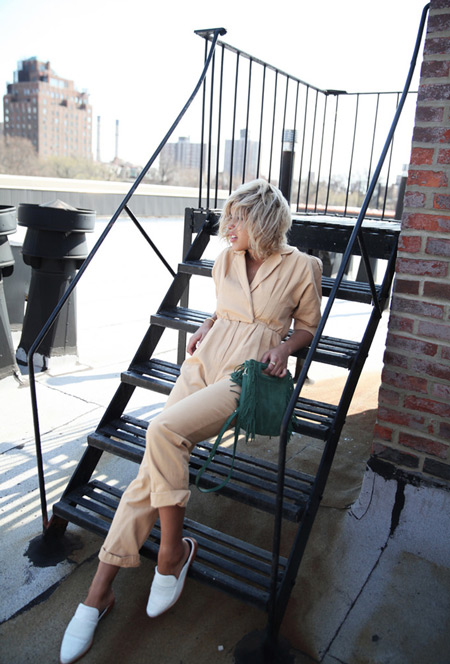 Модель в бежевом комбинезоне, белых сандалиях и зеленая сумка