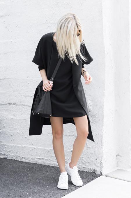 Модель в черном мини латье, плащ и белые кроссовки