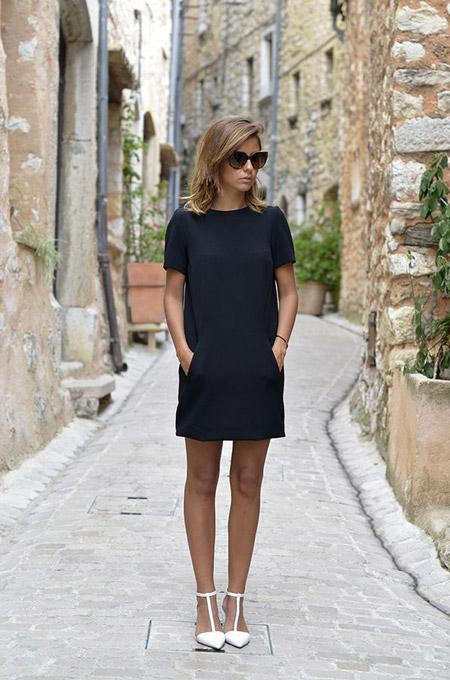Модель в черном мини платье с карманами и белые туфли