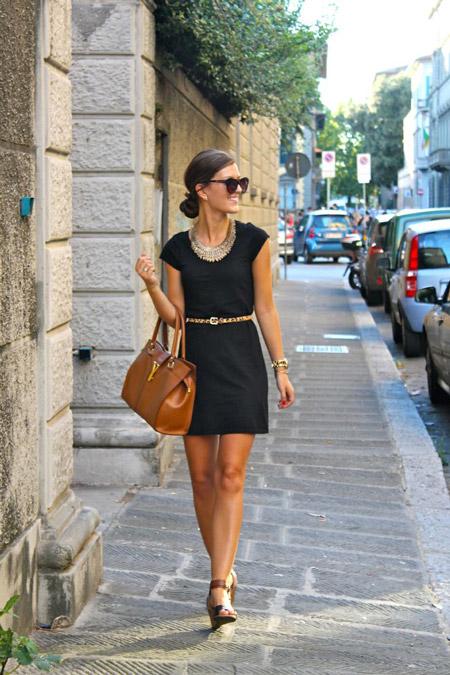 Модель в черном мини платье с ремешком на талии и объемная коричневая сумка