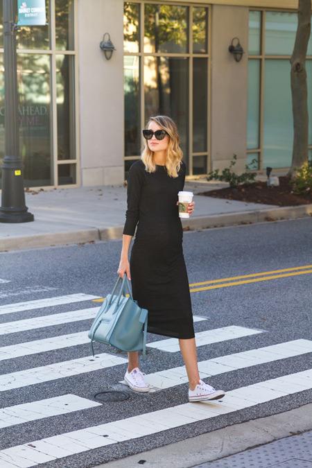 Модель в черном облегающем платье и объемная голубая сумка