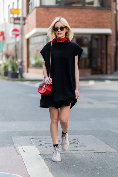 Модель в черном платье прямого покроя, красная сумочка и белые кеды