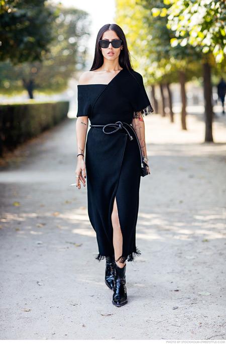 Модель в черном платье с ассиметричными плечами и глубоким разрезом