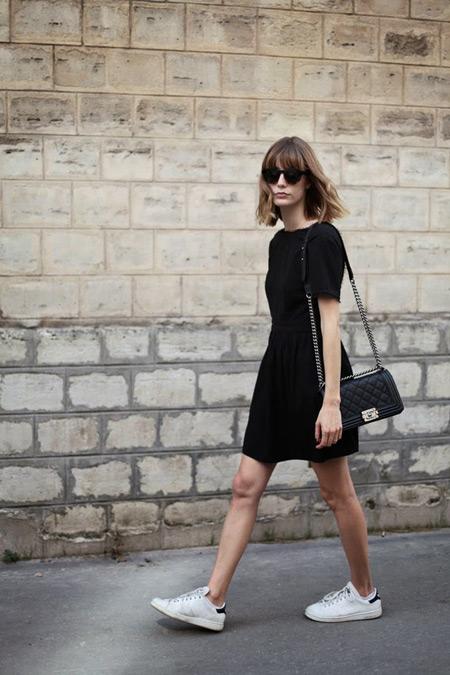 Модель в черном платье с коротким рукавом, сумочка и белые кроссовки