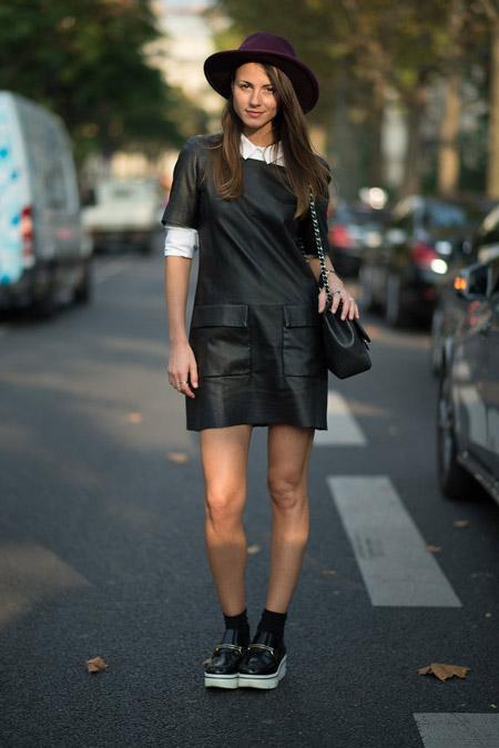 Модель в черном платье с накладными карманами, слипоны на белой подошве и бордовая шляпа