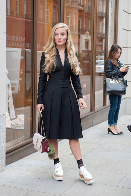 Модель в черном платье с плиссированой юбкой, белые слипоны