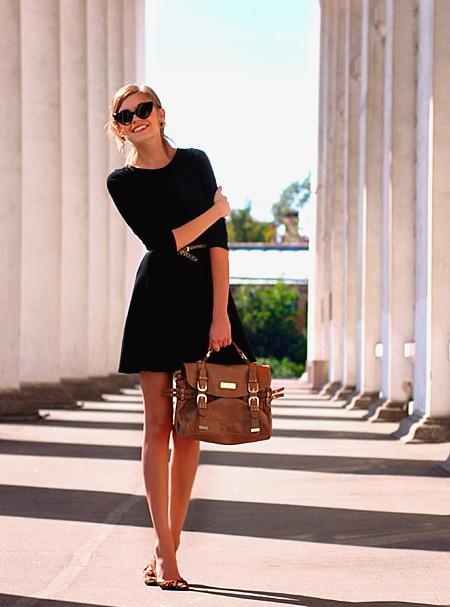 Модель в черном платье с ремешком на талии и коричневой сумкой