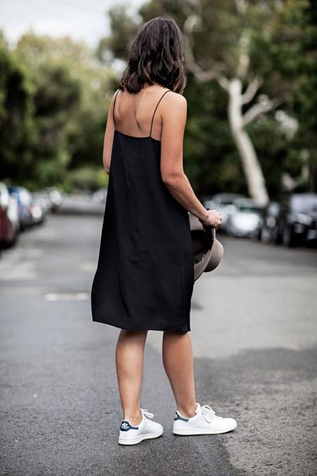 Модель в черном сарафане по колено и елые кросовки
