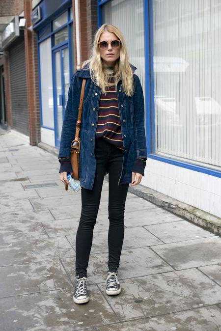 Модель в черных джеггинсах, полостая кофта, кеды и синяя джинсовая куртка