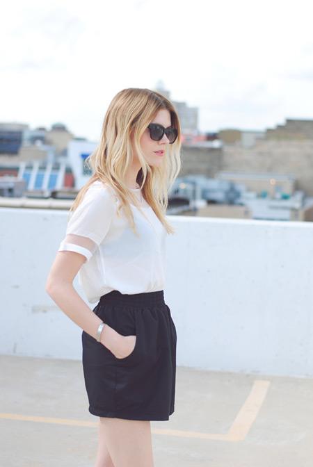 Модель в черных шортах и белой блузе с короткими рукавами